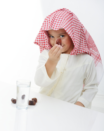A little muslim boy wearing islamic attire ready for braking Ramadan fast Stock Photo