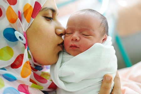 muslim woman: Beautiful new born baby in his mothers hands.