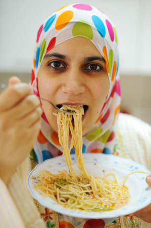 vermicelli: Young happy muslim woman with plate of spaghetti at kitchen