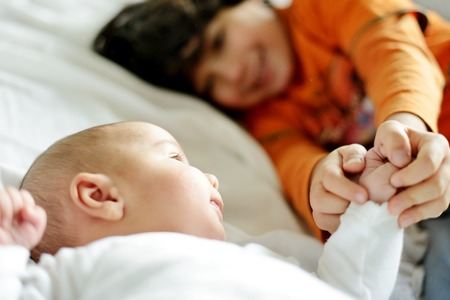 brother and sister: Little boy playing with his new newborn baby brother