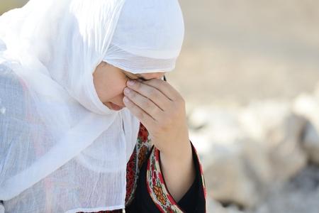 Desperate Arabic woman sitting on rock and crying Standard-Bild