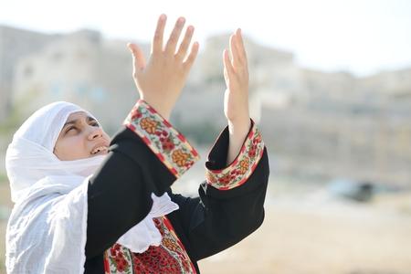 insurrection: Desperate Arabic woman praying