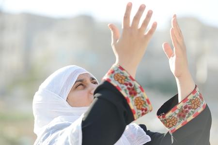 Desperate Arabic woman praying photo