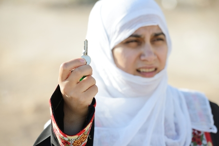 Desperate Arabic woman on Middle East holding key of lost home photo