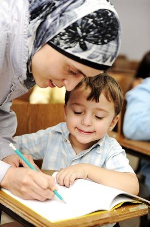 femme musulmane: Femme enseignante musulmane aider un petit élève dans la classe