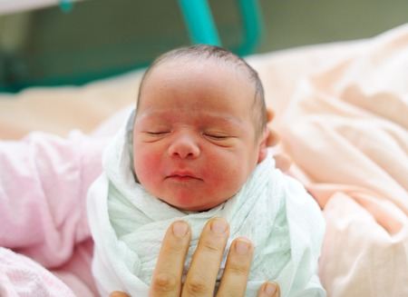 Beautiful new born baby in his mothers hands.