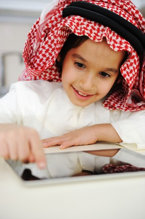 diversity children: Arabic little boy playing on tablet