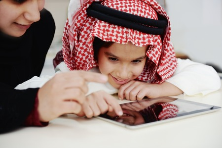 learning arabic: Arabic little boy and his mother working with touch tablet Stock Photo
