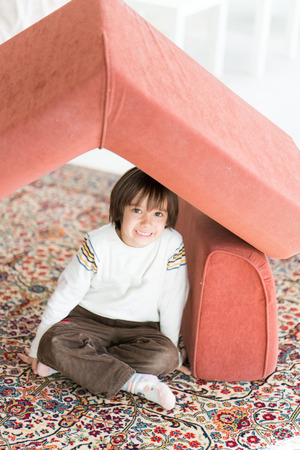 Little boy with long hair playing at home making house with roof of furniture on carpet