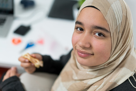Muslim teenage girl indoors eating snack
