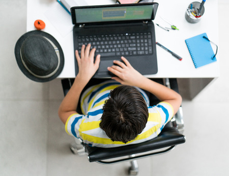 a young boy sitting on laptop at the desk