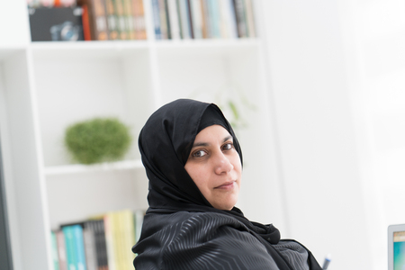 Young Muslim Woman Wotking on Laptop on Desk Imagens