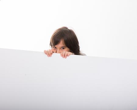 Little Caucasian Boy peeking behind White Boards