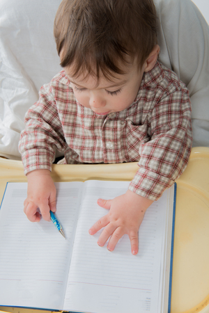 Little baby boy is playing with pen and note book