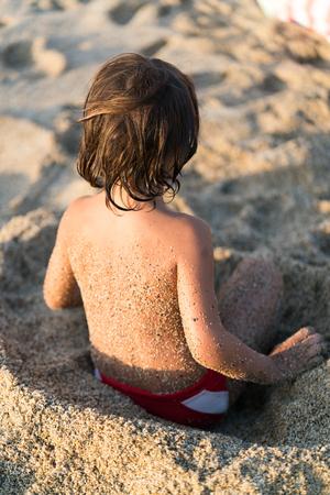 Child in sand on beach