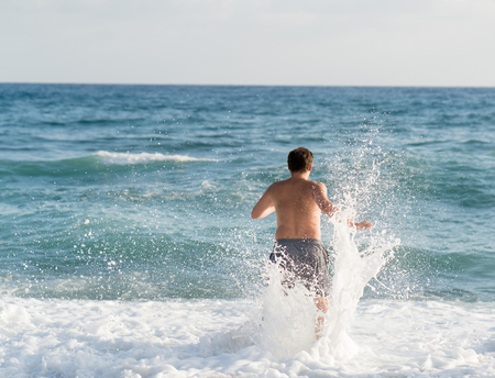 Man playing with waves on beach