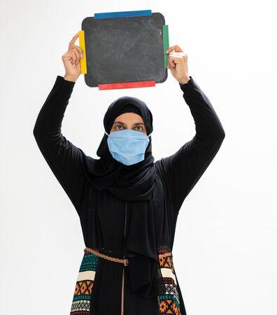 Muslim arab woman wearing mask and holding blank blackboard