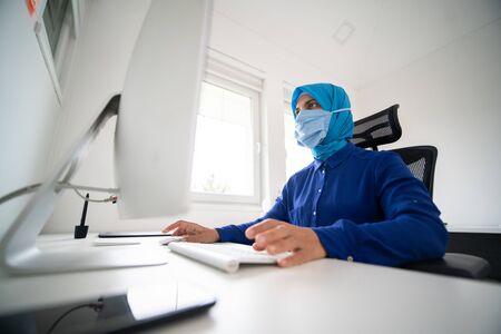 Muslim woman at laptop doing work