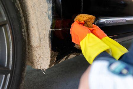 Hands of young boy washing car at home garage