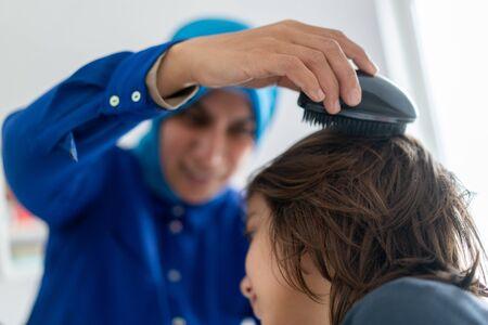 Muslim mother brushing hair of her son