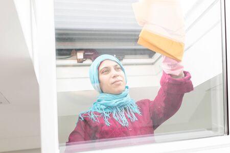 Muslim woman cleaning windows in living room Reklamní fotografie