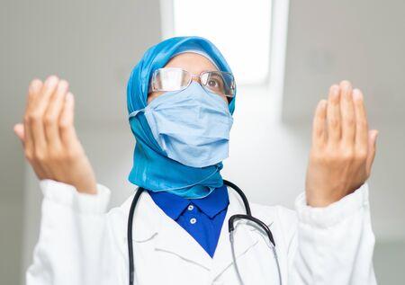 Muslim femal doctor praying for corona virus