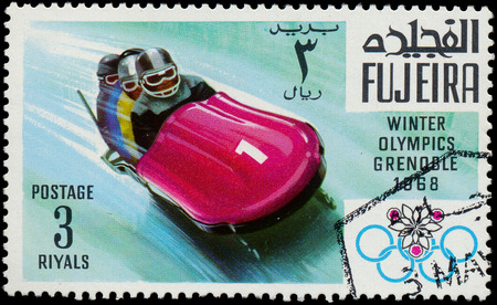 FUJEIRA - CIRCA 1968  A stamp printed in Fujeira shows bob team, devoted to the Winter Olympic Games in Grenoble, series, circa 1968