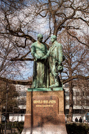 Cologne, North Rhine-Westphalia, Germany.March 2018.The statue in memory of Adolf Kolping, stands in front of the Minoritenkirche church in Cologne-Denkmal Adolf Kolping, Kolping-Platz, Koeln, Nordrhein-Westfalen, Deutschland Editorial