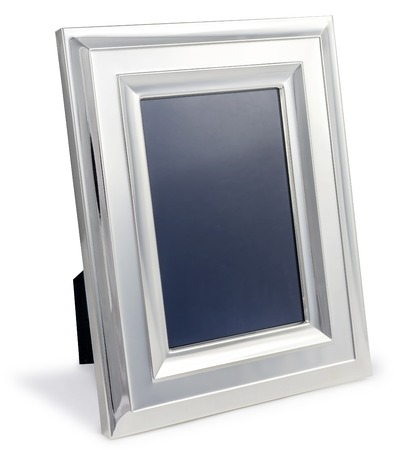 Leeg zilveren fotolijst aan het bureau met het knippen van weg op een witte achtergrond geïsoleerd Stockfoto