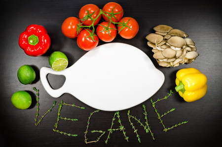 vegeterian: Blank white cutting board among the vegetables and text Vegeterian on the table. Top view