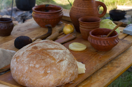 Ancient wooden and clay dishes  with hearth bread on a wooden table. Outdoor