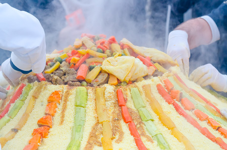 arabian food: Preparation of a large couscous outdoors. Moroccan street festival Stock Photo