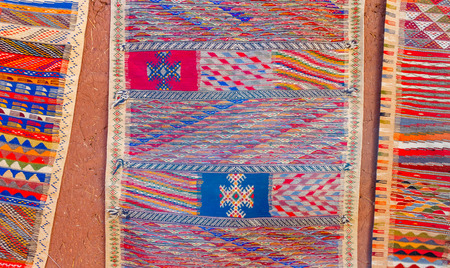 Colorful Moroccan Berber carpets hanging on adobe wall. Inside the ksar Ait Ben Haddou Stock Photo