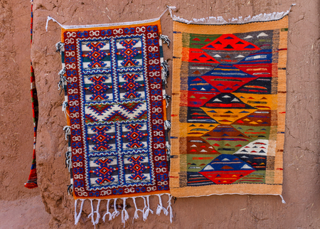 adobe wall: Colorful Moroccan Berber carpets hanging on adobe wall. Inside the ksar Ait Ben Haddou Stock Photo