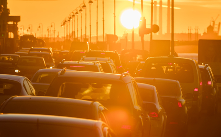 pileup: Cars are in a traffic jam during a beautiful golden sunset in a big sity. Stock Photo