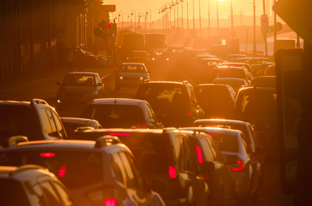 Cars are in a traffic jam during a beautiful golden sunset in a big sity. Stock Photo