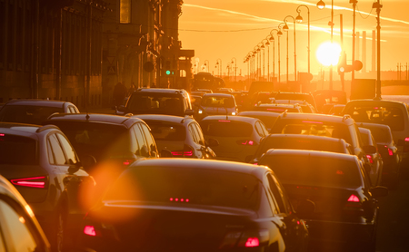 multiple lane highway: Cars are in a traffic jam during a beautiful golden sunset in a big sity. Stock Photo