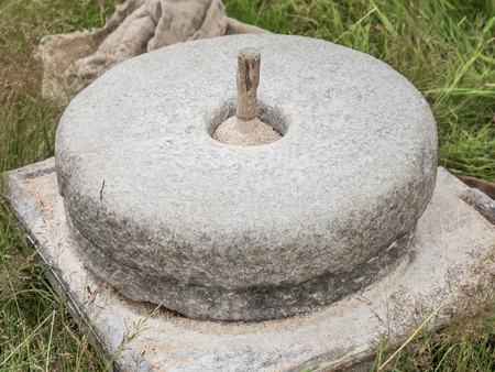 The ancient stone hand mill with grain and bag Stock Photo