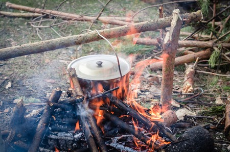 boiling pot: Cooking in the camp outdoor. Boiling pot on the fire with eggs Stock Photo