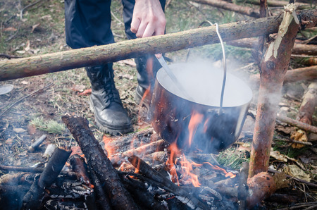 boiling pot: Cooking in the camp outdoor. Boiling pot on the fire with pancakes Stock Photo