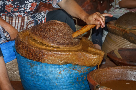 Moroccan worker preparing argan oil using stone mill Stok Fotoğraf