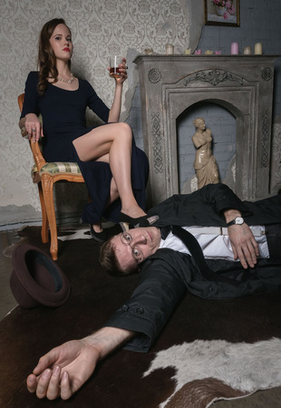 femme fatale: A scene from the film. Femme Fatale committed murder. The body of a man lying on the floor. Woman holding a glass of whiskey. Woman is sitting in armchair put her leg on guy Stock Photo