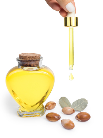 Argan oil. Bottle with oil. Cosmetic means. Food product. Jar with argan oil on the isolated background. Stock Photo