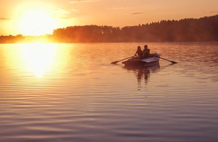 Een mooie gouden zonsondergang op de rivier. Liefhebbers rijden in een boot op een meer tijdens een prachtige zonsondergang. Gelukkige paarvrouw en man die samen op het water ontspannen. De prachtige natuur rondom. Rusland Ruza Reservoir Stockfoto