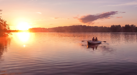 A beautiful golden sunset on the river. Lovers ride in a boat on a lake during a beautiful sunset. Happy couple woman and man together relaxing on the water. The beautiful nature around. Russia Ruza Reservoir Standard-Bild