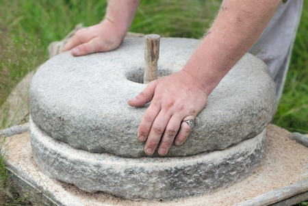 gristmill: The ancient Quern stone hand mill with grain. The man grinds the grain into flour with the help of a millstone. Mens hands on a millstone. Old grinding stones turned by hands