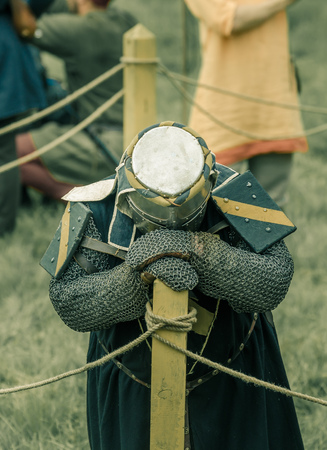 RITTER WEG, MOROZOVO, APRIL 2017: Festival of the European Middle Ages. Weary knight in helmet and chainmail resting after battle bending his head.