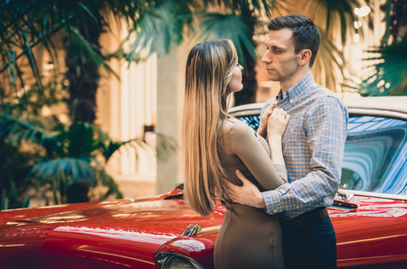 A romantic couple is standing by the red car. A man is hugging a woman. American classics. The guy and the girl next to the red car. Californian dream concept.