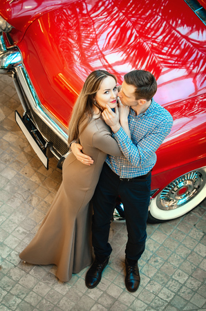 californian: A romantic couple is standing by the red car. A man is hugging a woman. American classics. The guy and the girl next to the red car. Californian dream concept.