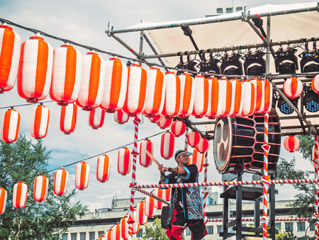 Moscow, Russia - July 16, 2017: Musicians ASKA-GUMI play the taiko drums on scene yagura During the japanese festival. Paper red-white lanterns Chochin Scenery for the holiday Obon